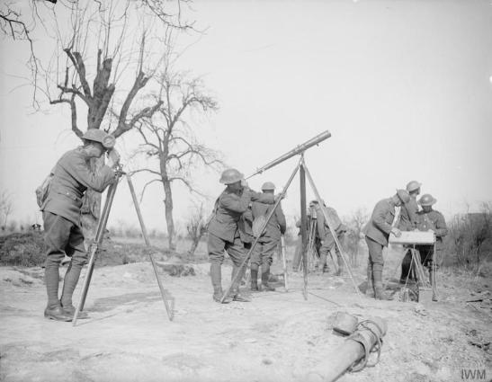 Men of an anti-aircraft battery using telescopes to verify identification range finders and range table, for the guns at St. Vaast, 13 March 1918. © IWM (Q 8557)