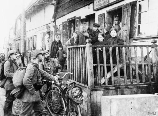 Troops of a German cyclist detachment speaking with Polish villagers outside a shop, 1915. Gorlice-Tarnow © IWM (Q 53609)