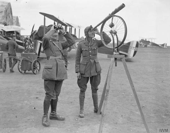A telescope on a stand improvised from a front wheel of a bicycle on a wooden tripod. Aerodrome at Rang du Fliers, 12 July 1918. © IWM (Q 12083)