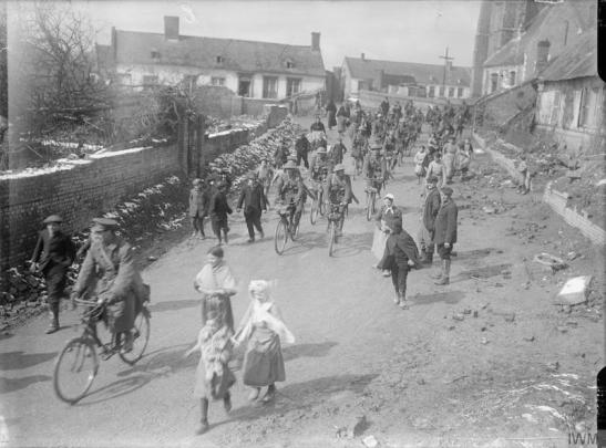 © IWM (Q 1879)  Cyclists passing through the village of Vraignes (Vraignes-en-Vermandois), March 1917. They were the first British troops to enter.