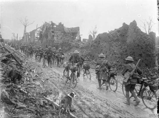 Cyclists passing through the ruined village of Brie, March 1917. © IWM (Q 1868)