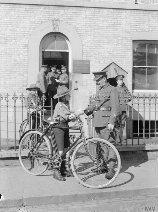 A boy scout working as a military despatch cyclist during the First World War. © IWM (Q 30596)