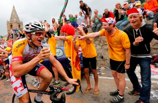 Lotto-Belisol team rider Adam Hansen of Australia drinks a glass of beer as he climbs the Alpe d'Huez mountain during the 172.5km eighteenth stage of the centenary Tour de France cycling race from Gap to l'Alpe d'Huez, in the French Alps, July 18, 2013.           REUTERS/Jean-Paul Pelissier