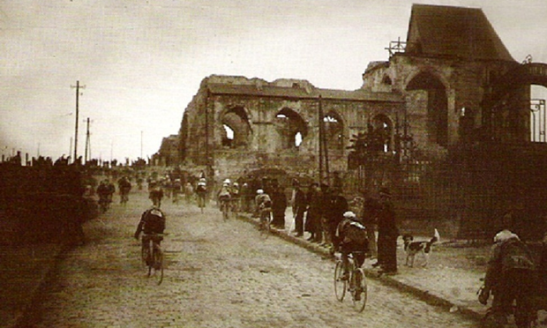 Riders pass shattered ruins during Paris-Roubaix, 1919. Photograph PR
