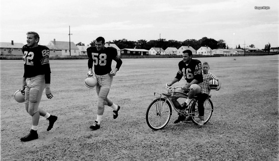 Hank Gremminger (46) riding a bike with an unidentified boy on the back while defensive end Jim Temp (82) and linebacker Dan Currie (58) lead the way to the practice field. © Keegan Wright