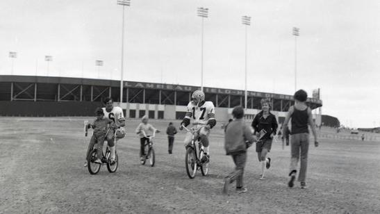 Quarterbacks Scott Hunter (16) and Jerry Tagge (17) ride bicycles loaned to them by young fans from Lambeau Field to their practice field during training camp in Green Bay, 1973 © AP Photo/Wisconsin Historical