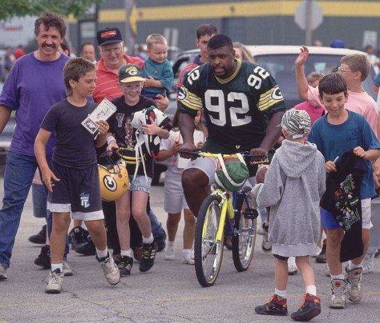 Defensive end Reggie White surrounded by fans in 1993. © John Biever/SI