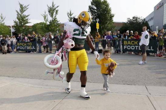 Running back DuJuan Harris accompanied by a young Packers fan and her monkey, 2014. © Morry Gash/Associated Press.